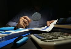 Auditor checks financial report with magnifying glass. Internal audit and business analysis