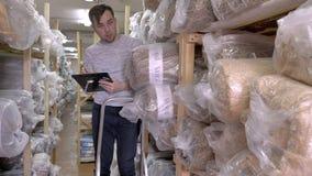 Auditor Counts Merchandise in Pakhuis Hij loopt door Rijen van Opslagrekken met Koopwaar Langzame Motie stock videobeelden