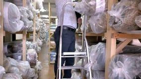 Auditor Counts Merchandise in Pakhuis Hij loopt door Rijen van Opslagrekken met Koopwaar Langzame Motie stock footage