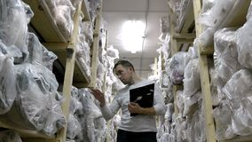 Auditor counts merchandise in warehouse. He walks through rows of storage racks with merchandise. Slow motion. 4k stock footage
