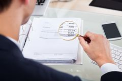Auditor examining invoice with magnifier Royalty Free Stock Photo