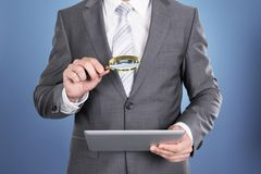 Auditor holding magnifying glass and tablet Royalty Free Stock Images