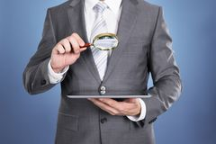 Auditor holding magnifying glass and tablet Stock Image