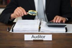 Auditor Scrutinizing Financial Documents no escritório Fotografia de Stock