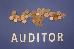 Auditor written with wooden letters on a blue background. To mean a business concept Royalty Free Stock Photos