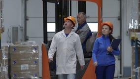 Auditoren door Rijen van Opslagrekken met Koopwaar in Pakhuis Langzame Motie stock video