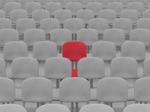 Auditorium. Digital render of an empty auditorium of grey chairs with a single red chair Stock Image