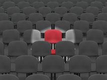 Auditorium. Digital render of an empty auditorium of grey chairs with a single red chair lit by a spotlight Stock Image