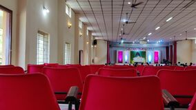 Auditorium hall interior at the day of wedding function includes red chairs rotating fans and colored lights with peoples and deco