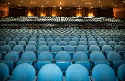 Auditorium with rows of blue seats with railing in back royalty free stock images
