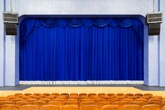 The auditorium in the theater. Blue curtain on the stage. Blue-brown chair. Room without people.  Royalty Free Stock Photography