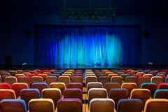 The auditorium in the theater. Blue-green curtain on the stage. Multicolored spectator chairs. Lighting equipment.  Royalty Free Stock Photography