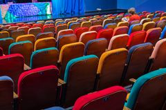 The auditorium in the theater. Multicolored spectator chairs. One person in the audience.  Royalty Free Stock Photography