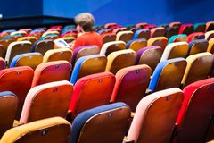 The auditorium in the theater. Multicolored spectator chairs. One person in the audience Royalty Free Stock Photos