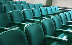 Auditory seats. Green old seats of an auditory, theatre green cozy seats with fabric over it and metallic arms and structures, texture background stock images