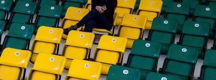 Audytorium w sportach powikłanych z plastikowymi siedzeniami Dziewczyna z telefonem komórkowym w jej ręce siedzi na żółtym siedze zdjęcia stock