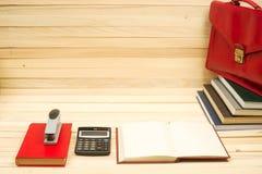 Auf Büchern eines Holztischs Dokumente, Taschenrechner, roter Aktenkoffer Lizenzfreie Stockbilder