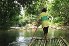Auf Bambusflössen auf einem Gebirgsfluss in Khao- Lakpark flößen, Thailand Mann steuert das Floss mit einem langen Pfosten, hinte stockbild