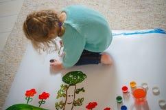 Auf dem Boden, den Farben, dem Mädchen, den Blumen und dem Baum sitzen Stockfoto