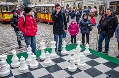 Auf dem ein enormes Schachbrett der Kampf in den Turnierkindern, die im Freien mit den weißen und schwarzen Stücken auf der Straß Lizenzfreies Stockbild