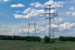 Auf dem Gebiet gibt es Türme für Hochspannungsleitungen Hinter einem blauen Himmel mit Kumuluswolken Lizenzfreie Stockbilder