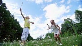 Auf dem Grün Kamillenrasen, Mädchen, Kinder, Badminton spielend, Sie stranden, springen, täuschen Sie haben Spaß Sommer stock video footage