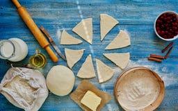Auf dem hölzernen Küchentisch ist geschnittener Teig Stockfotos