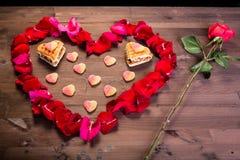 Auf dem Holztisch gibt es eine Rosarose und ein Herz von rosafarbenen Blumenblättern, Lizenzfreie Stockfotos