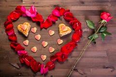 Auf dem Holztisch gibt es eine Rosarose und ein Herz von rosafarbenen Blumenblättern, dessen Innere Plätzchen in Form von Herzen  Stockfotos