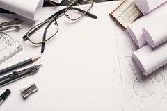 Auf dem Holztisch gibt es Zeichnungen, Kompassse, Bleistift, Gummiband, Machthaber, Bleistiftspitzer und Gläser lizenzfreies stockfoto