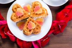 Auf dem Holztisch innerhalb des Herzens der rosafarbenen Blumenblätter sind zwei Lizenzfreie Stockbilder