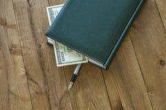 Auf dem Holztisch liegt ein Tagebuch mit einem Stift und ein Teil des MOs Stockfotos