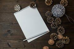 Auf dem Holztisch sind ein Notizbuch, verziert mit Kiefernkegeln, einem Weihnachtsball und einem Bleistift Stockfotografie
