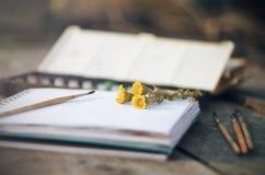 Auf dem Holztisch sind gelbe Blumencoltsfoot- und -kunstversorgungen lizenzfreie stockfotos