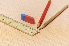Auf dem Millimeterpapier sind zwei einfache Bleistifte, ein Radiergummi und a Stockfoto