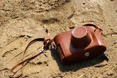 Auf dem nass Sand ist eine Kamera in einer braunen ledernen Abdeckung, Reise im Sommer verloren lizenzfreie stockfotografie