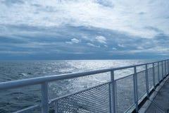 Auf dem Oberdeck eines Schiffs mit der Eisenbahn befördern, laufend mit dem Horizont und dem erstaunlichen blauen Himmel im Abst stockfotografie