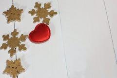 Auf dem roten Herzen des weißen Hintergrundes gemacht vom Stoff und von den goldenen Schneeflocken Lizenzfreies Stockbild