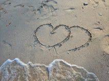 Auf dem Sand gibt es das Zeichnen mit zwei Herzen Ist unten Wellen einer Blase kommen zu einem wenig Raum, Sommerkonzept Rote Ros lizenzfreie stockbilder