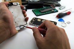 Auf dem Schreibtisch Schlosser Preparing, Hauptknopf ฺButton des Handys ist zu ändern beschädigt worden Stockfotografie