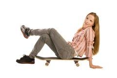 Auf dem Skateboard sitzen, oben schauend Stockfotos