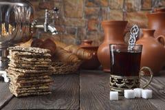 Auf dem Speisetische seien Sie: ein Samowar, ein Glas mit Tee in einem Bronzeschalehalter, neue Rollen, Plätzchen und alte kerami Stockfotografie