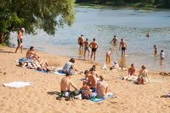 Auf dem Strand stillstehende und schwimmende Leute Stockfoto
