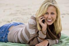 Auf dem Strand und am Telefon Stockfotografie
