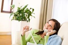 Auf dem Telefonhaus: Lächelnde Frau, die im Aufenthaltsraum benennt lizenzfreie stockfotografie