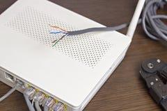 Auf dem Tisch das Netzkabel und das Modem, Router Lizenzfreie Stockfotos