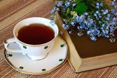 Auf dem Tisch ein Buch, ein Blumenstrauß von Blumen und eine Tasse Tee stockfoto