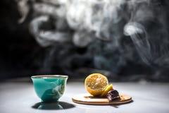 Auf dem Tisch ein Gewehr und ein Tee mit Zitrone Stockbilder