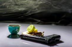 Auf dem Tisch ein Gewehr und ein Tee mit Zitrone stockbild