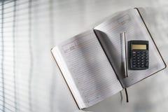 Auf dem Tisch in einem offenen Tagebuch und in einem Stift mit einem Taschenrechner Stockfotografie